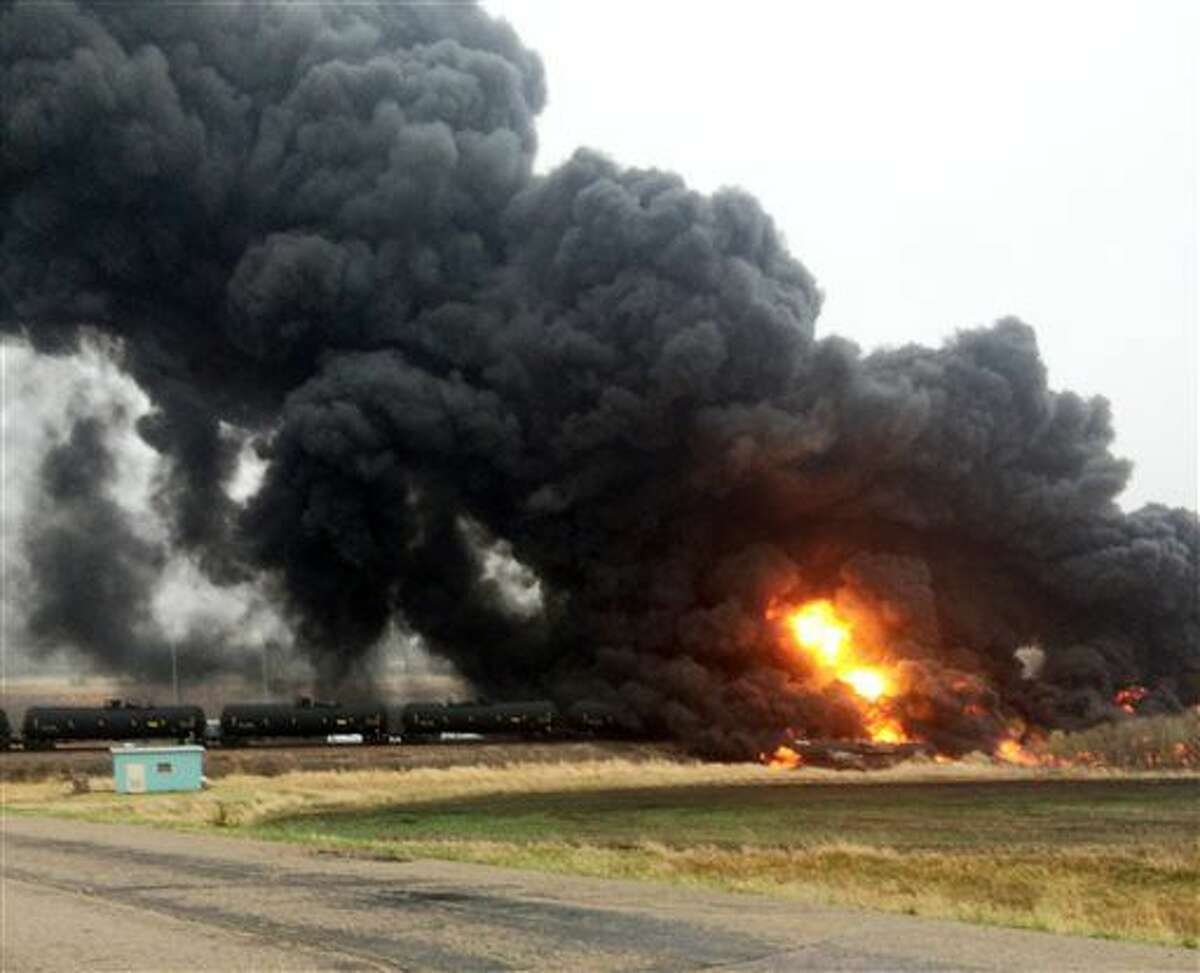 CORRECTS NAME OF SOURCE TO CURT BENSON INSTEAD OF CURT BEMSON - This photo provided by Curt Benson shows smoke and fire coming from an oil train that derailed, Wednesday, May 6, 2015, in Heimdal, N.D. Officials say ten tanker cars on the BNSF caught fire prompting the evacuation of Heimdal where about three dozen people live. No injuries were reported. (Curt Benson via AP)