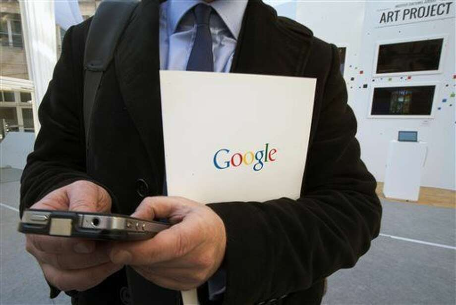FILE - In this Dec. 10, 2013 file photo, a reporter uses his smartphone during a presentation for the new Google cultural institute in Paris. More Google search requests are now being made on mobile devices than personal computers in the U.S. and many other parts of the world. The milestone was announced at a digital advertising conference on Tuesday, May 5, 2015. (AP Photo/Jacques Brinon, File) Photo: Jacques Brinon