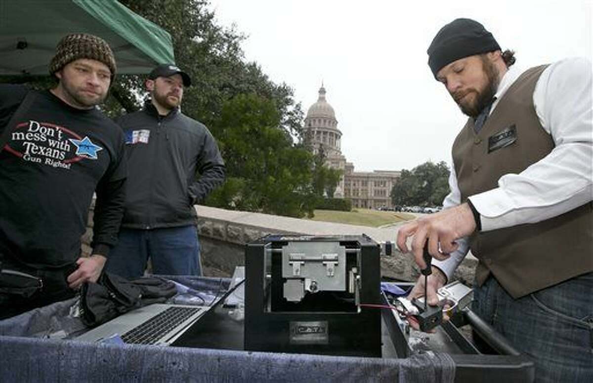 Mudoch Pizgatti, right, of Plano, uses the Ghost Cutter CNC machine by Defense Distributed to manufacture a lower receiver for an AR-15 gun at a rally to support HB195, a bill relating to the open carrying of handguns, at the Capitol in Austin, Texas, on Tuesday Jan. 13, 2015. Pizgatti said the homemade gun would not have a serial number. Watching are, left to right, Matthew Short of Fort Worth and Phoenix Horton of Denton. (AP Photo/Austin American-Statesman, Jay Janner) AUSTIN CHRONICLE OUT, COMMUNITY IMPACT OUT, INTERNET AND TV MUST CREDIT PHOTOGRAPHER AND STATESMAN.COM, MAGS OUT