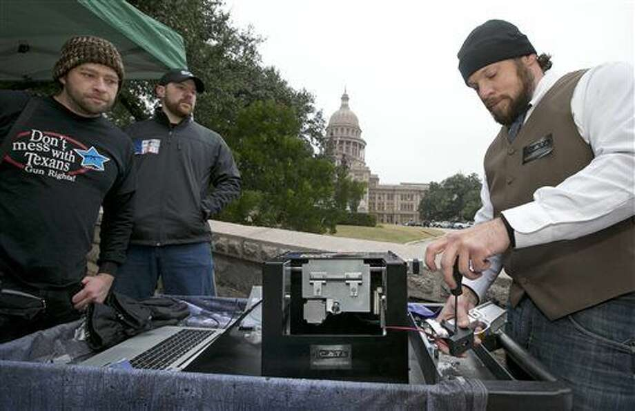 Mudoch Pizgatti, right, of Plano, uses the Ghost Cutter CNC machine by Defense Distributed to manufacture a lower receiver for an AR-15 gun at a rally to support HB195, a bill relating to the open carrying of handguns, at the Capitol in Austin, Texas, on Tuesday Jan. 13, 2015. Pizgatti said the homemade gun would not have a serial number. Watching are, left to right, Matthew Short of Fort Worth and Phoenix Horton of Denton. (AP Photo/Austin American-Statesman, Jay Janner) AUSTIN CHRONICLE OUT, COMMUNITY IMPACT OUT, INTERNET AND TV MUST CREDIT PHOTOGRAPHER AND STATESMAN.COM, MAGS OUT Photo: Jay Janner