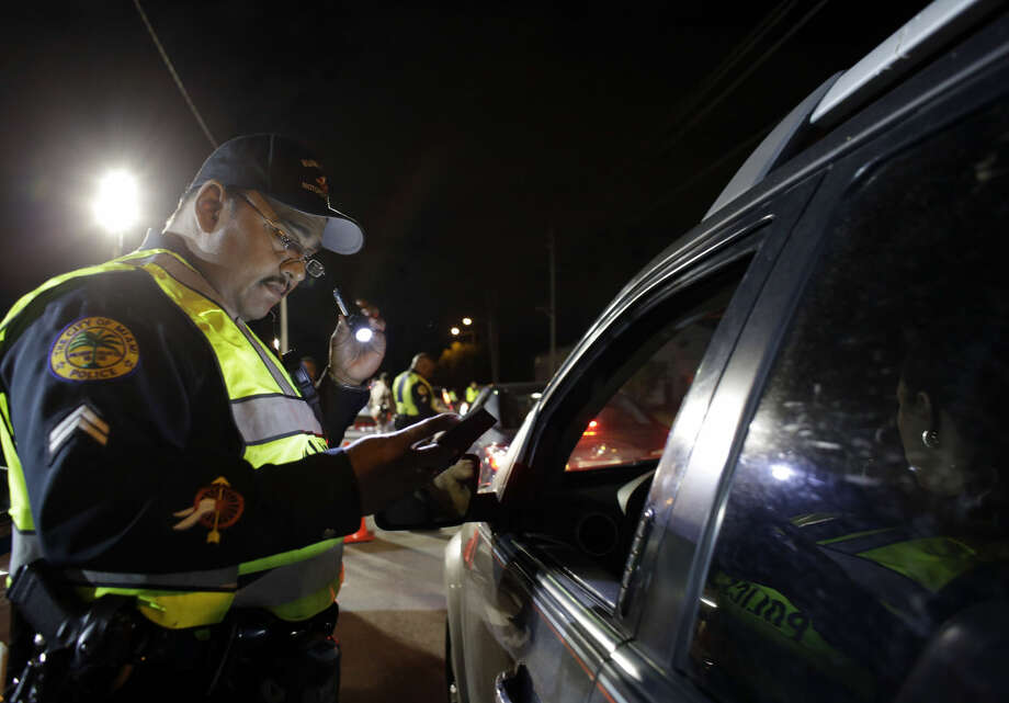In this Thursday, Jan. 29, 2015 photo, Miami police officer Luis Ortiz looks at a driver's license he requested from a motorist during a drunk-driving checkpoint in Miami. A South Florida DUI attorney contends the commonly-used checkpoints violate driver's constitutional rights. (AP Photo/Lynne Sladky) Photo: Lynne Sladky