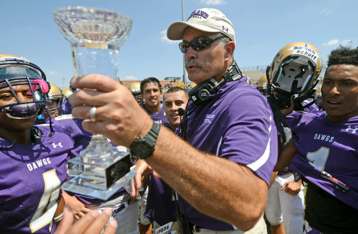 Midland football head coach Craig Yenzer hands the trophy to his team after a win against EP Americas Saturday at Grande Communications Stadium. James Durbin/Reporter-Telegram