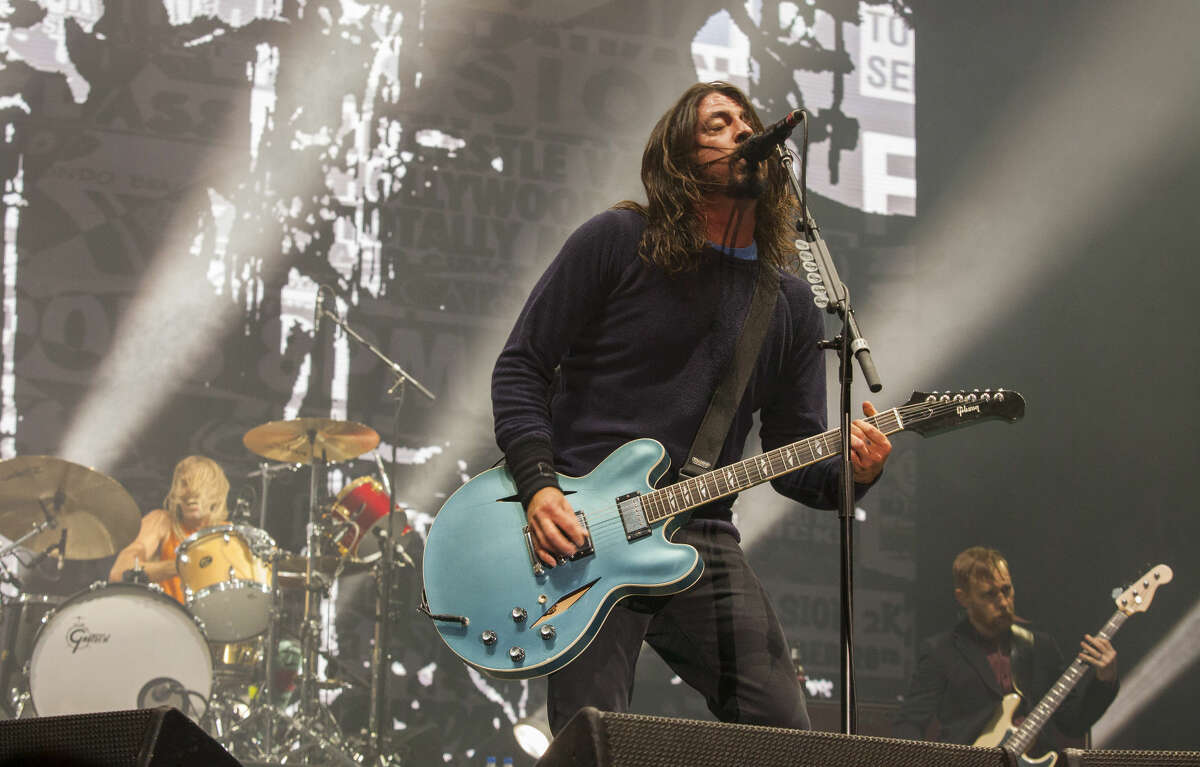 In this Nov. 2, 2014 file photo, Taylor Hawkins, Dave Grohl and Nate Mendel of the Foo Fighters perform at the Voodoo Music Experience in New Orleans.