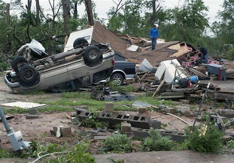 Workers survey the damage as clean-up begins Monday, May 11, 2015, in the aftermath of at least one tornado that moved through the area on Sunday, May 10, 2015, in Van, Texas. The community was reeling following a series of storms, including at least one tornado, struck the North Texas community, leaving two dead and dozens more injured or missing Sunday evening, May 10, 2015. (Andrew D. Brosig/The Tyler Morning Telegraph via AP) Photo: Andrew D. Brosig