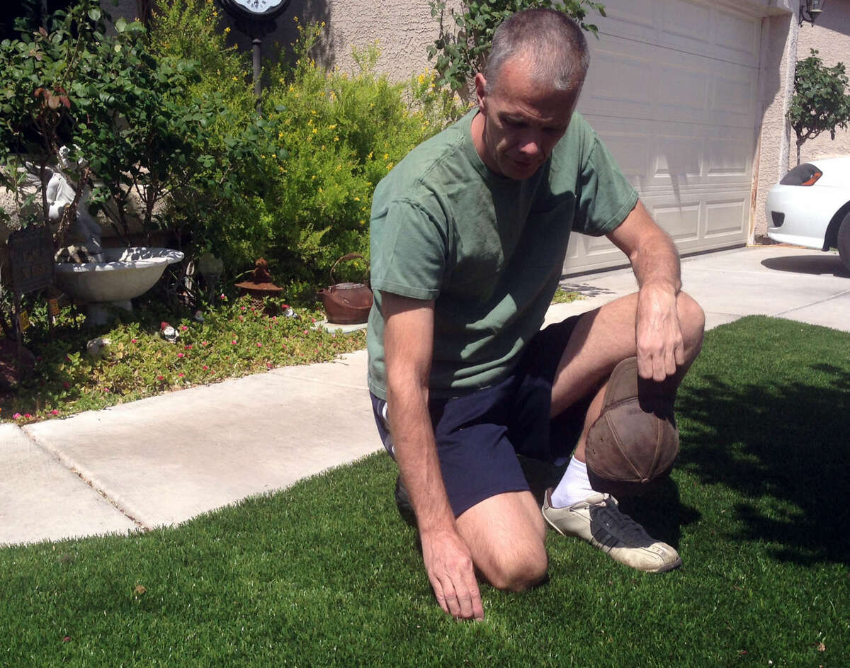 Ron Newsome recently installed artificial grass on his North Las Vegas lawn to conserve water during the ongoing drought. Neighbors think it's real. Here he poses and relaxes on the turf he calls