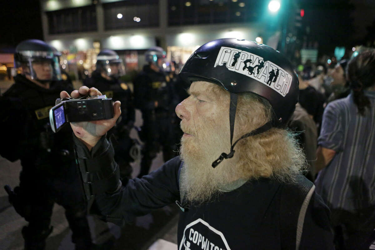 A protester films California Highway Patrol officers on University Avenue in Berkeley on Monday, December 8, 2014.