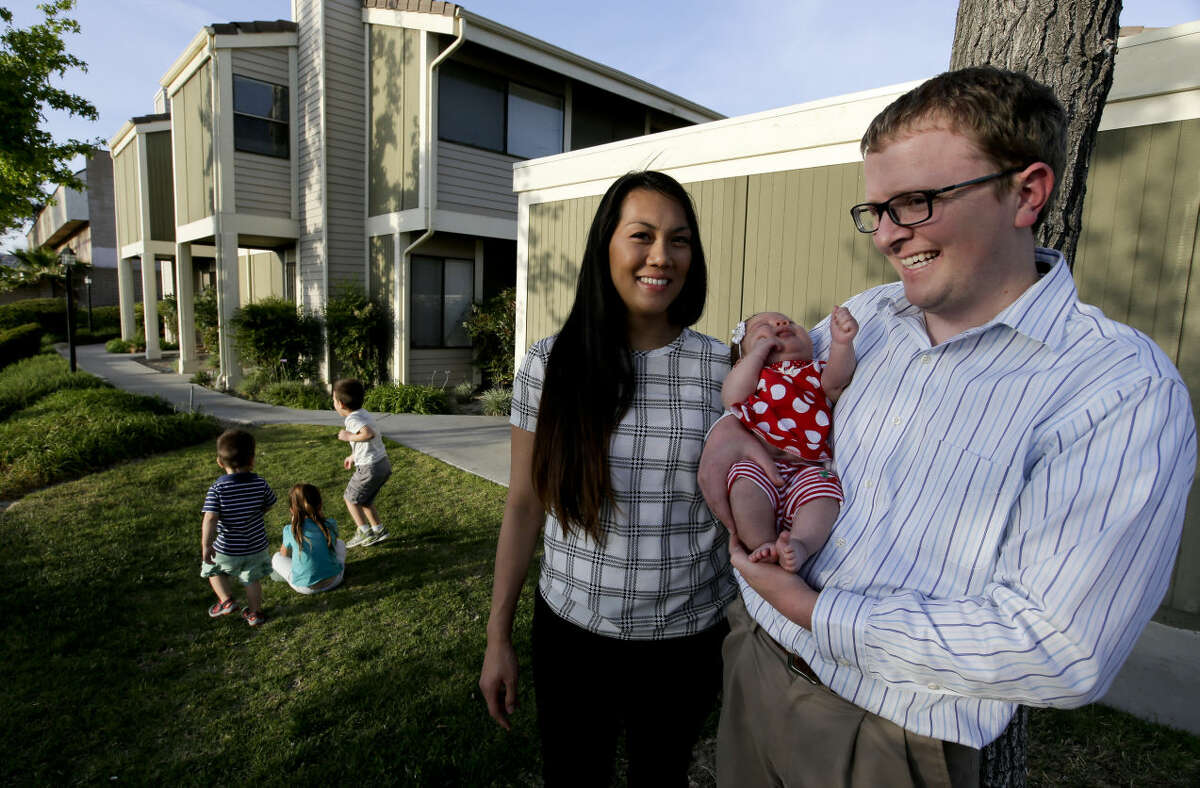 In this May 11, 2015 photo, Brett Singley, right, poses for a picture in front of their condo with his wife Angelynn 28, and their children, Ben 2, Isla 5, Aria 1 month, and Isaiah 3, in Santa Clarita, Calif. Singley bought the three-bedroom home for just under $300,000 - $100,000 less than what he was prepared to pay for a house. (AP Photo/Chris Carlson)