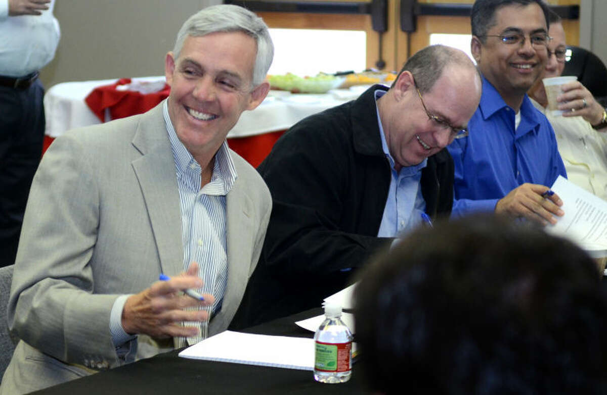 (File Photo) From left, Mayor Wes Perry shares a laugh with city councilman Jeff Sparks and Jose Ortiz, director of engineering services, before the start of a meeting at the Junior League of Midland Wednesday. James Durbin/Reporter-Telegram