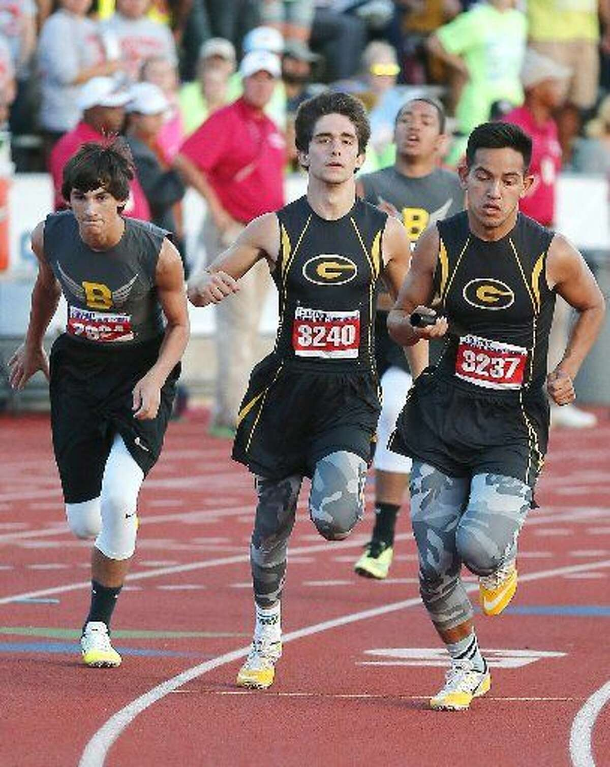 Grady Joseph Briseno, far right, grabs the baton from Beau Lucas on the third leg of the 800 relay Friday at the UIL State Track and Field Championships.
