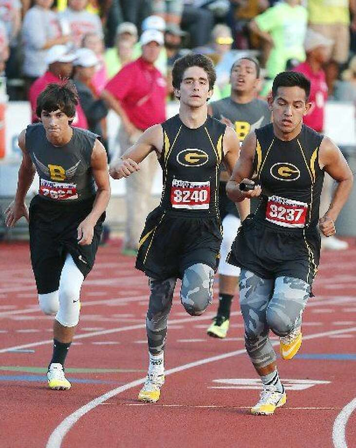 Grady Joseph Briseno, far right, grabs the baton from Beau Lucas on the third leg of the 800 relay Friday at the UIL State Track and Field Championships. Photo: Wade H. Clay