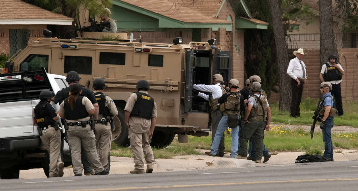 Members of MPD SWAT and sheriff deputies wait outside a residence Wednesday, 5-20-15, in the 4400 block of Thomason Drive for a suspect they were trying to serve a warrant. The suspect was not in the duplex. Tim Fischer\Reporter-Telegram