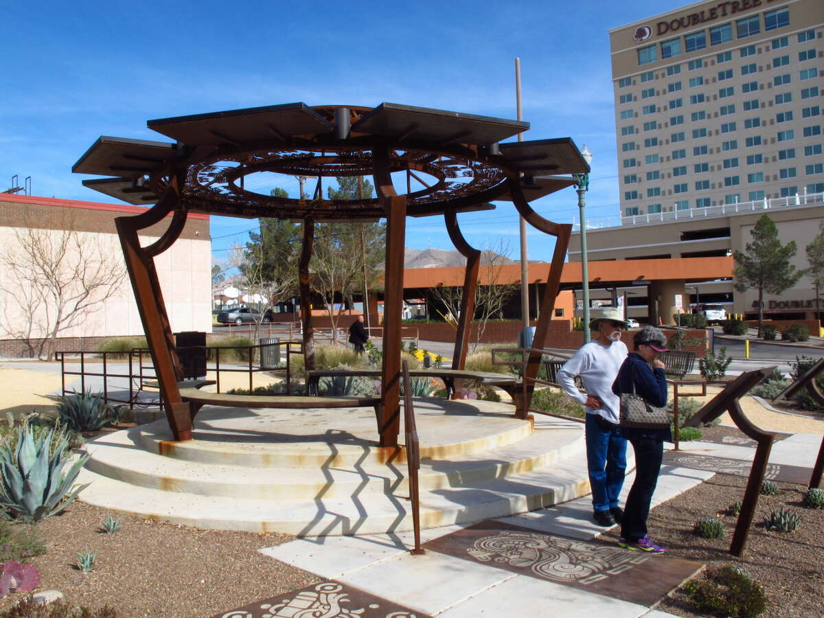Downtown El Paso pedestrians can charge their electronic devices for free using 12 solar-powered outlets beneath benches in the Aztec Calendar Pavilion in the city's arts district. The charging station is one of numerous ways El Paso officials are making the city more green. (AP Photo/Betsy Blaney)