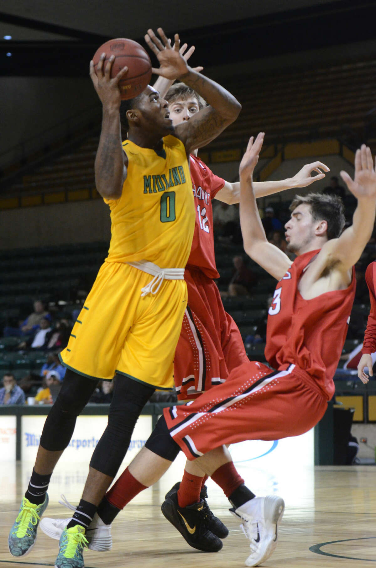 Midland College's Torren Jones (0) attempts to score against Howard College as Will Ferguson tries to draw a foul Thursday, Jan. 29, 2015 at Chaparral Center. James Durbin/Reporter-Telegram