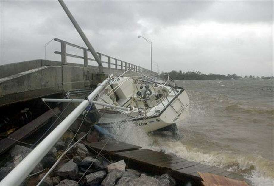 FILE - In this Sept. 16, 2004 file photo, waves crash against a sailboat lodged under a bridge in Fort Walton Beach, Fla., after Hurricane Ivan struck the gulf coast. Federal regulators believe a persistent oil spill in the Gulf of Mexico that began after a drilling platform was toppled during Hurricane Ivan in 2004 will continue for 100 years or more if left unchecked, according to estimates obtained by The Associated Press that provide new details about the extent of the problem. (AP Photo/John Bazemore, File) Photo: John Bazemore