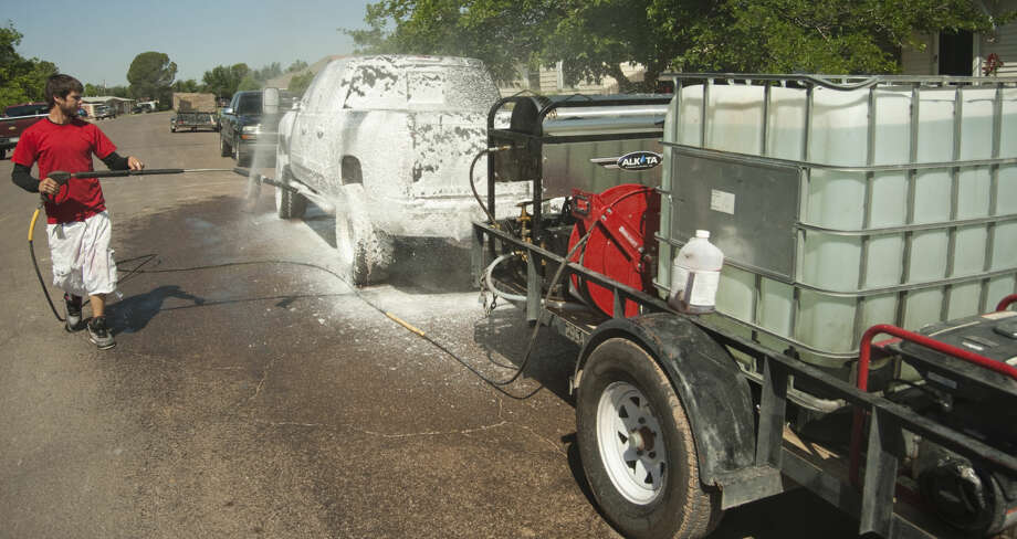 Michael Portillo, with Basin Steaming, washes down the company truck Tuesday, 5-26-15, morning as they get set to head out to clean other cars around Midland between a lull in the storms. Tim Fischer\Reporter-Telegram Photo: Tim Fischer