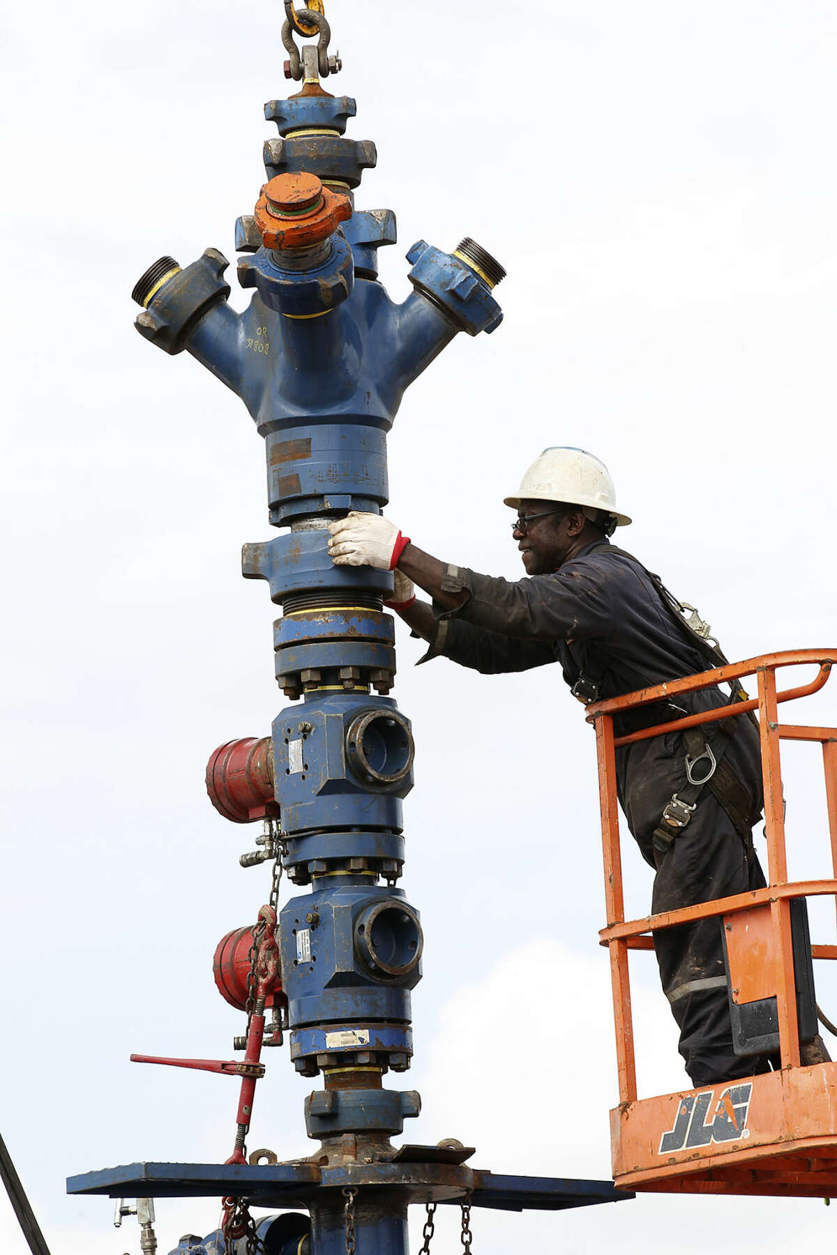 Nathen (cq) George removes a frac tree from a well on a ranch southwest of Ben Bolt, Texas, on Wednesday, Sept. 11, 2013. The well, located near the Jim Wells and Duvall County line, was drilled to a depth of over one mile.