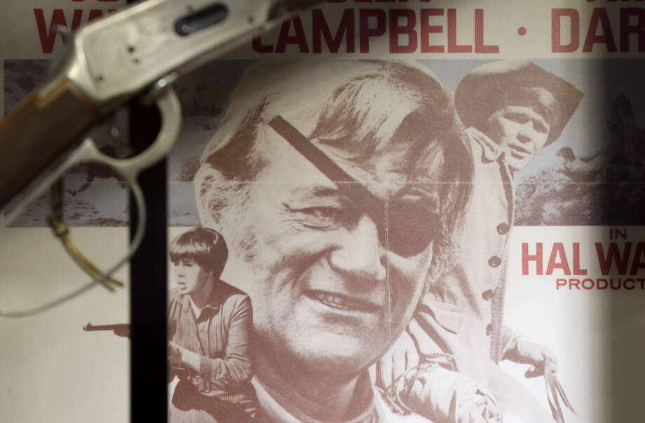 "A movie poster from True Grit is shown in a display case in the John Wayne Museum, Thursday in Winterset, Iowa. Tuesday would have been the Hollywood legend's 108th birthday. The Texas Legislature declared it ""John Wayne Day in Texas."" Photo: Charlie Neibergall/AP"