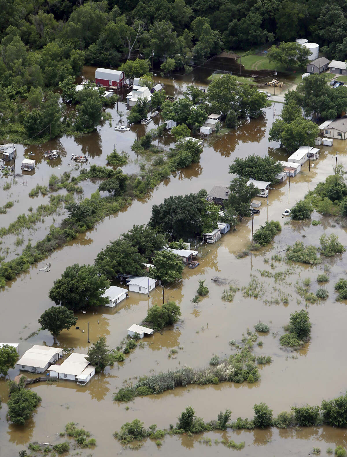 Flood waters from the Brazos River inundate a residential area, Friday, May 29, 2015, in Granbury, Texas. Floodwaters submerged Texas highways and threatened more homes Friday after another round of heavy rain added to the damage inflicted by storms. (AP Photo/Brandon Wade)