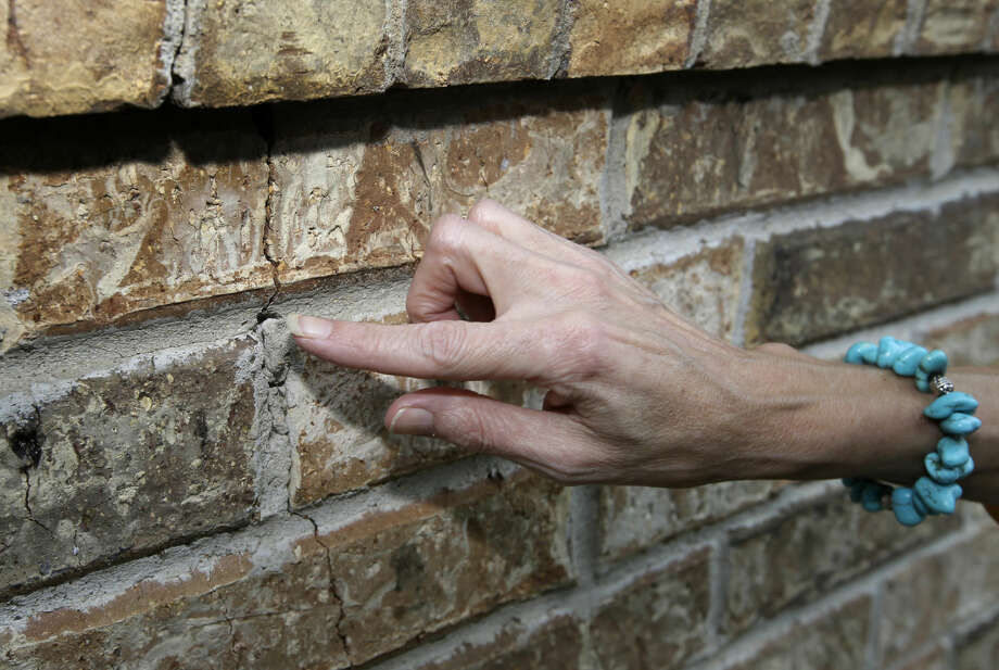 Barbara Brown points to a one of several cracks on an exterior wall of her home, Saturday, June 21, 2014, in Reno, Texas. Brown said that she believes the cracks to her homes foundation and wall as related to the natural gas drilling in the area. (AP Photo/Tony Gutierrez) Photo: Tony Gutierrez