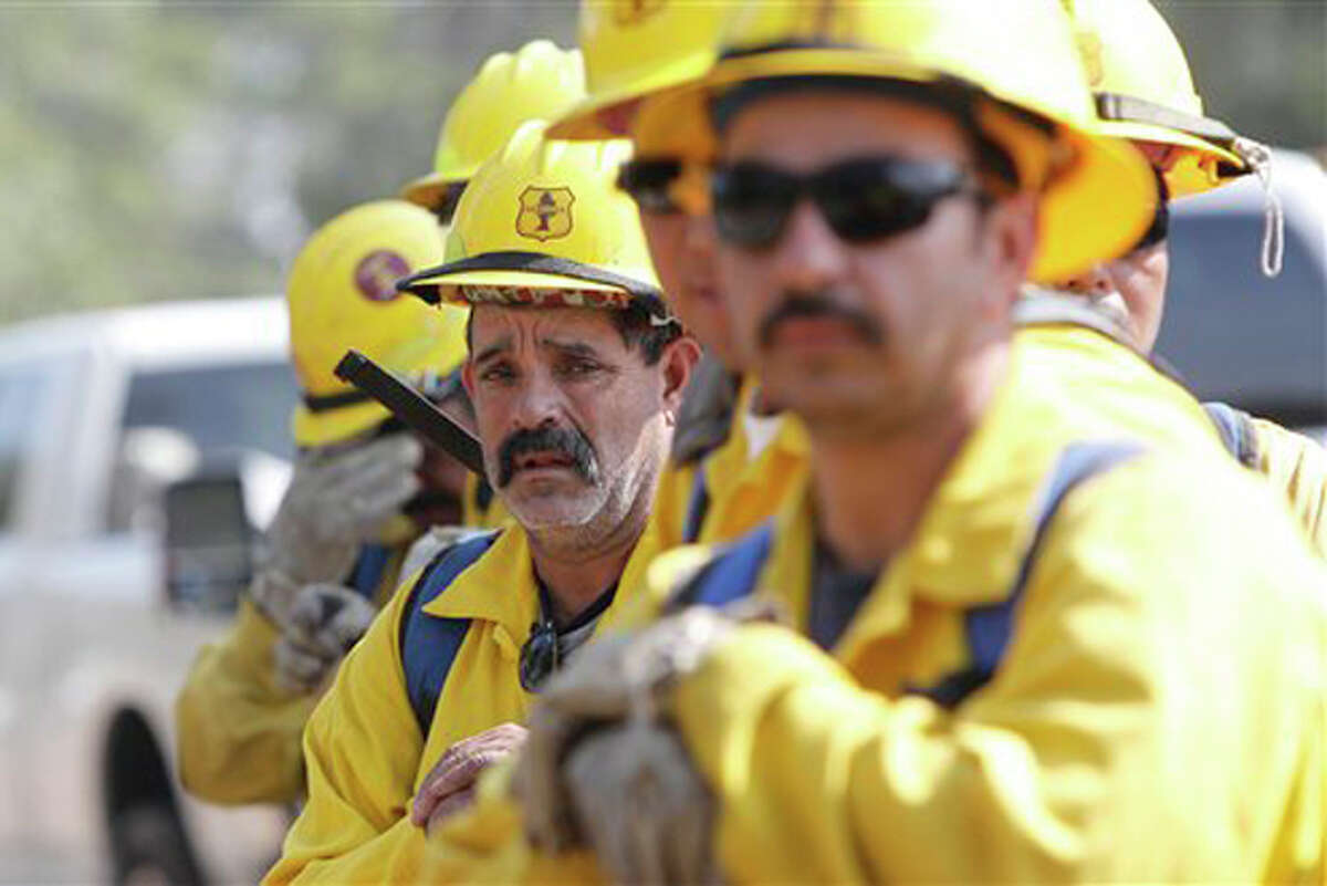 A fresh team of firefighters just arrived from the Sequoia National Forest in California line up to march in and douses hot spots on the fire near Bastrop, Texas, Friday, Sept. 9, 2011. (AP Photo/LM Otero)