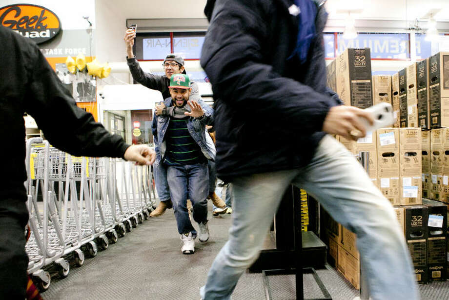 Luis Estrada carries Jerry Gutierrez into Best Buy after camping out with friends Diego Lopez and Alex Olivas (in foreground) for Black Friday deals on Thursday. Best Buy opened at 6 p.m. James Durbin/Reporter-Telegram Photo: JAMES DURBIN