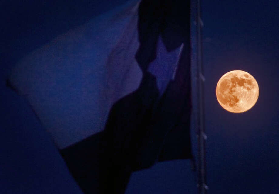 "The Texas flag flies in front of a full moon August 20, 2013. August's full moon, which rose on Tuesday can be correctly identified as a ""Blue Moon,"" a ""Full Sturgeon Moon,"" a ""Full Red Moon,"" a ""Green Corn Moon and a ""Grain Moon."" It qualifies as a Blue Moon because it's the third full moon in a season with four (most seasons have only three). The title of Full Sturgeon Moon refers to the annual August full moon because the large fish called sturgeon can most easily be caught at this time of year. The title of Full Red Moon comes from the reddish tint of the moon as it rises caused by atmospheric conditions this time of year. The last title, Green Corn Moon or Grain Moon, are interchangeable and refer to the crops that grow tallest at this time of year. James Durbin/Reporter-Telegram Photo: JAMES DURBIN"