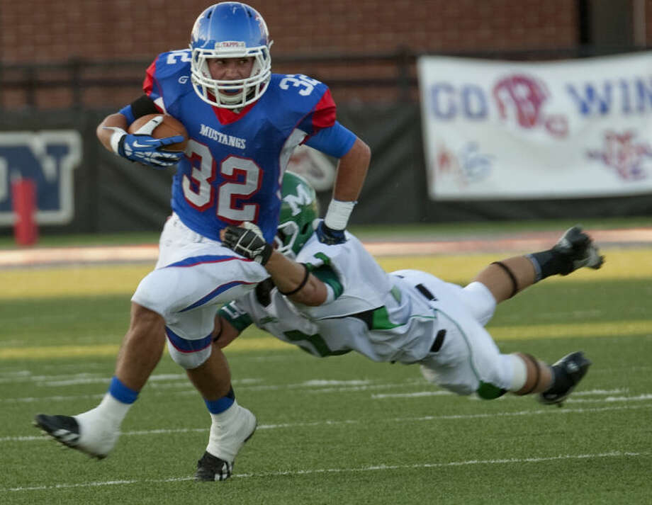 Midland Christian's Justin Fender looks upfield for more yards as Monahans' Kristian Crozier hangs on Friday night at Mustang Field. Tim Fischer\Reporter-Telegram Photo: Tim Fischer