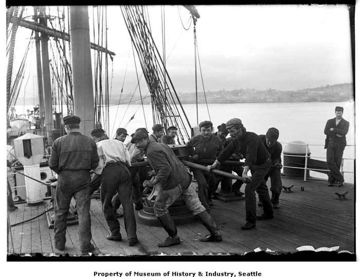 """""""Before the introduction of steam engines to pull up anchors or move heavy weights, sailors had to use muscle power. Stout levers were placed in the holes of a capstan, and the men pushed on the levers to turn the capstan. The turning of the capstan wound up the anchor chain. This photo shows a group of men lifting an anchor with a capstan. It was taken in somewhere in the northern Pacific Ocean, probably around 1900. The age of sail was ending by this time."""" -MOHAI. Photo courtesy MOHAI, Seattle Historical Society Collection, image number shs1444."""