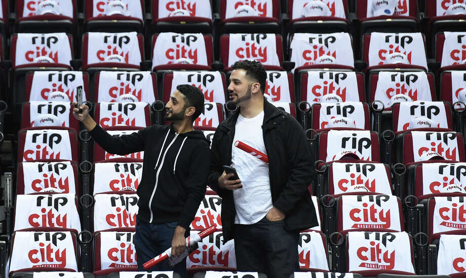 "Portland fans take photos while surrounded by T-shirts with the Jim Barnett-inspired ""Rip City"" slogan. / 2016 Getty Images"