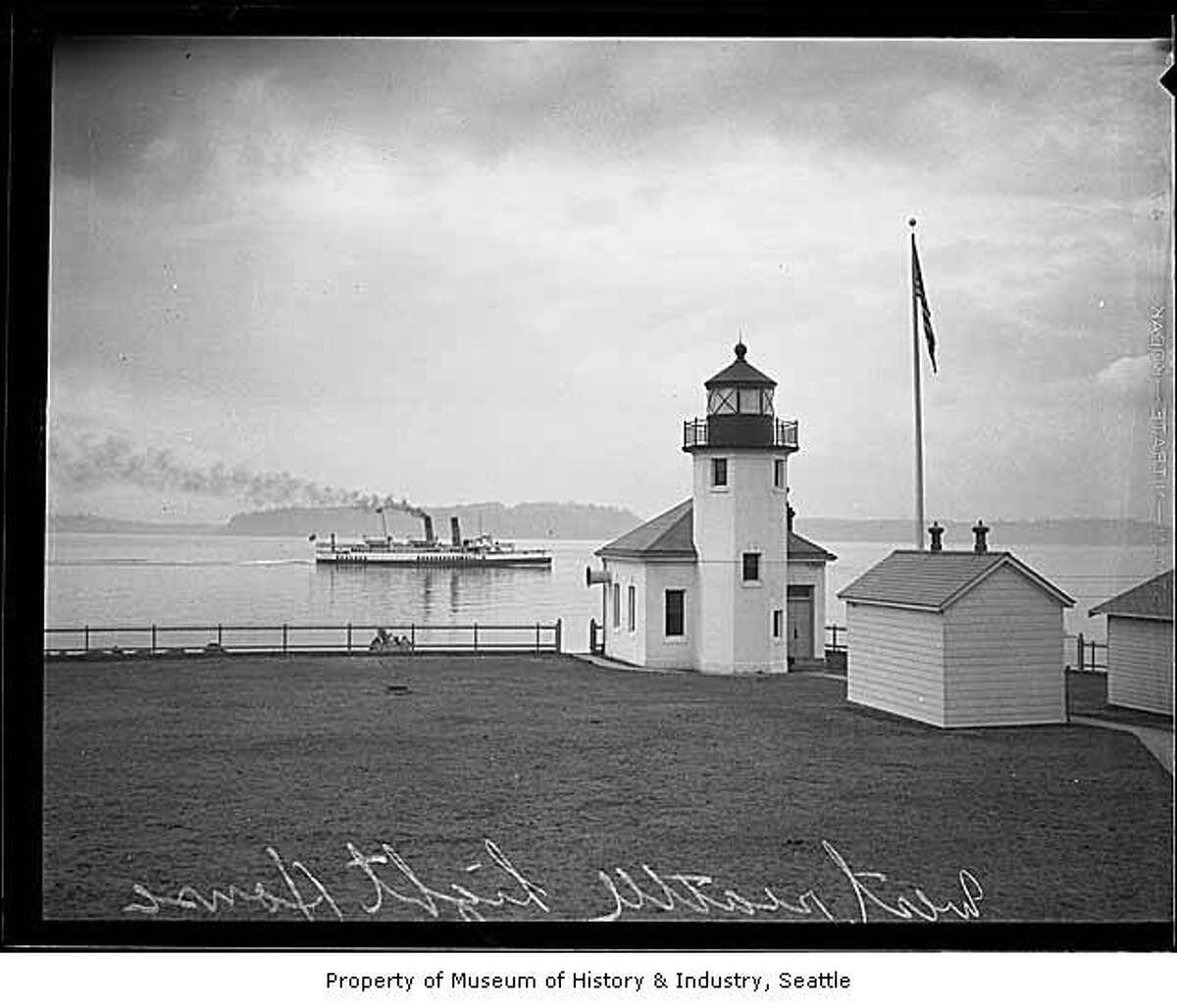 """""""The point of land originally known as Sma-Qua-mooks and Point Roberts was low and hard to see from a ship, so the need for a guiding light became evident. By 1858, the place was called Battery Point, and a single kerosene lantern was hung on the lonely shore by members of Hans Hanson's family. In 1887, the U.S. Lighthouse Service recognized the need for a stronger light, so they took over the task and erected a 10-foot brass post lantern. A new lighthouse station, including a small stucco building with a brick tower at the end of the point, began operating in 1913. The structure remains today."""" -MOHAI. Photo, dated 1931, courtesy MOHAI, Seattle P-I Collection, image number 1986.5.7176.1."""