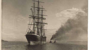 """In the 19th and early 20th centuries, sailing ships carried lumber from the northwest to ports all over the world. Moving in and out of ports in Puget Sound could be tricky for these large vessels. They often depended on tugboats to tow them. In this photo, taken in 1906 by Webster & Stevens photographer Homer Davidson, the lumber freighter ""Ganges"" is being towed by two tugboats. The vessel was headed to pick up a load of lumber at Port Blakely. Its crew then signed on at Port Townsend, and the ship sailed to Callao, Peru to deliver the lumber. The home port of the ""Ganges"" was Tvedestrand, Norway."" -MOHAI. Photo courtesy MOHAI, PEMCO Webster and Stevens Collection, image number 1983.10.PA7.26."