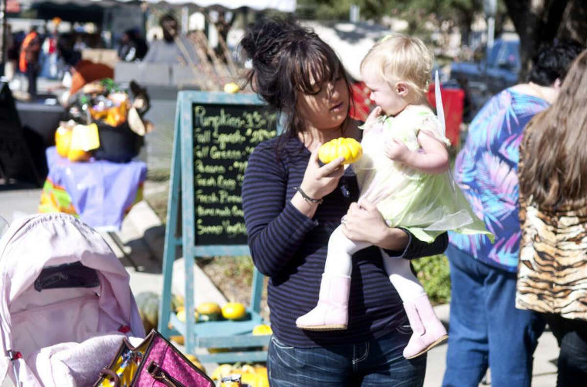 Shelby Miller and daughter Jennifer, age 1.5, shop at the Farmer's Market in downtown Midland on Saturday. James Durbin/Reporter-Telegram