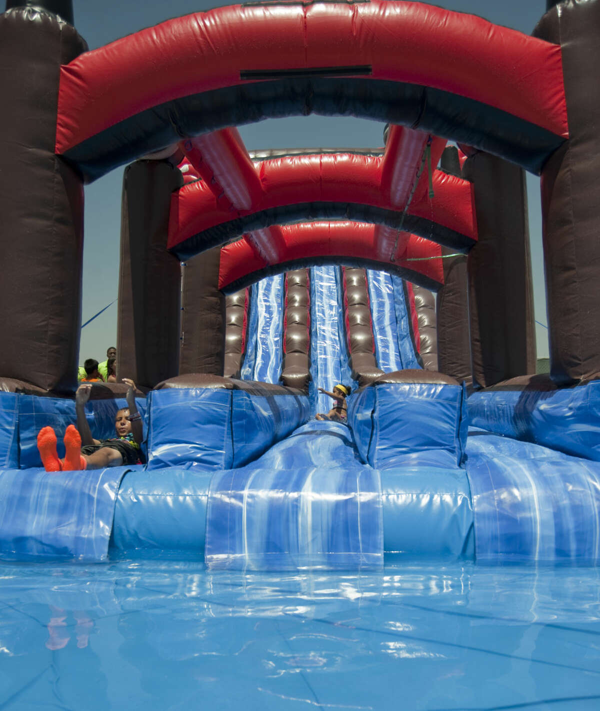 Special guests try out the Tiki Island Inflatable Water Park Thursday, 6-4-15, during an invite only soft opening to help employees get ready for the grand opening Saturday next to Grande Communications Stadium. Tim Fischer\Reporter-Telegram