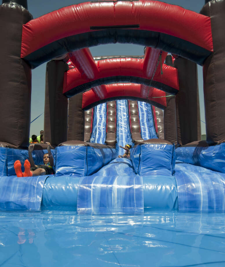 Special guests try out the Tiki Island Inflatable Water Park Thursday, 6-4-15, during an invite only soft opening to help employees get ready for the grand opening Saturday next to Grande Communications Stadium. Tim Fischer\Reporter-Telegram Photo: Tim Fischer