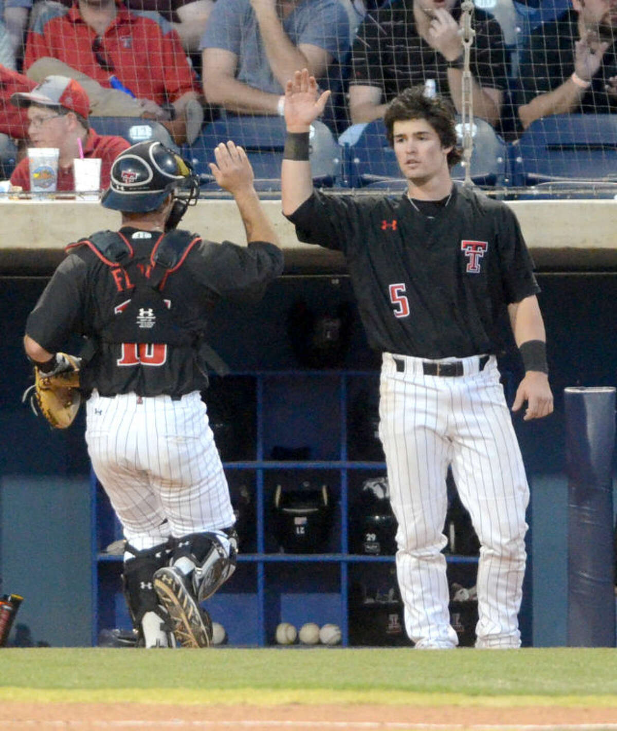 Texas Tech catcher Hunter Redman (5) high-fives catcher Tyler Floyd as he returns to the dugout between innings during a non-conference game against New Mexico on Tuesday at Security Bank Ballpark. James Durbin/Reporter-Telegram