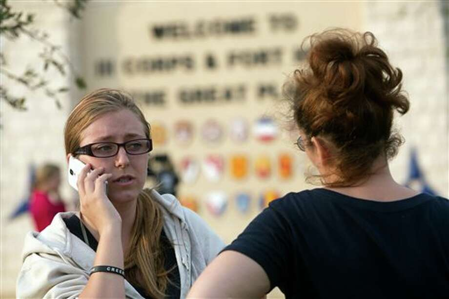Krystina Cassidy, left, and Dianna Simpson attempt to make contact with their husbands who are stationed inside Fort Hood while standing outside of the Bernie Beck Gate on Wednesday, April 2, 2014, in Fort Hood, Texas. At least one person was killed and 14 injured in the shooting, and officials at the base said the shooter is believed to be dead. (AP Photo/ Tamir Kalifa) Photo: Tamir Kalifa / FR170773 AP
