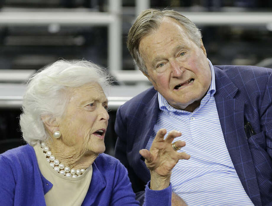 FILE- In this March 29, 2015, photo, former President George H.W. Bush and his wife Barbara Bush speak before the first half of a college basketball game in Houston. The former first lady is promoting literacy on her 90th birthday by lending her backing to a $7 million challenge by X Prize and Dollar General. They're challenging developers to create a mobile app to help improve adult literacy skills. (AP Photo/David J. Phillip, File)