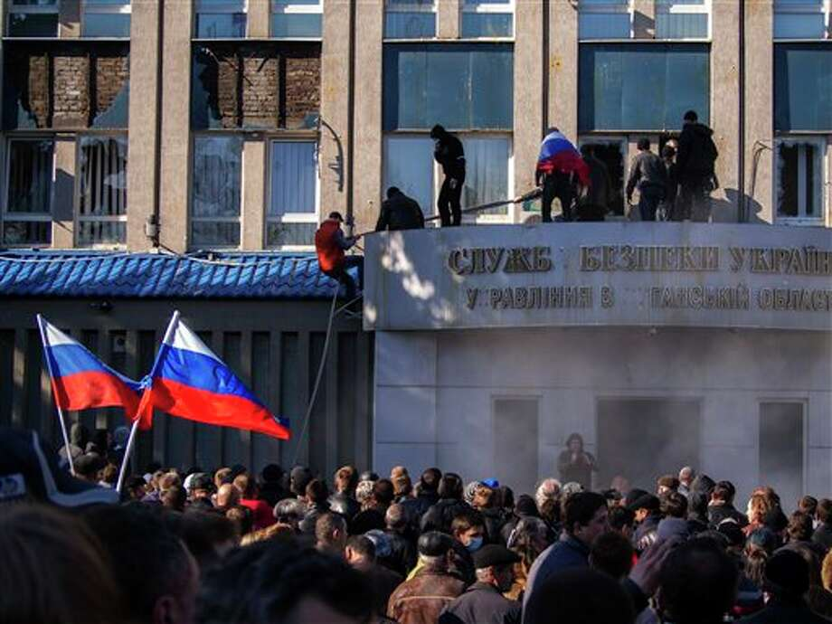 Pro-Russian activists with Russian national flags storm the Ukrainian regional office of the Security Service in Luhansk, Ukraine, Sunday, April 6, 2014. In Luhansk, 30 kilometers (20 miles) west of the Russian border, hundreds of people surrounded the local headquarters of the security service and later scaled the facade to plant a Russian flag on the roof. (AP Photo/Igor Golovniov) Photo: Igor Golovniov / AP
