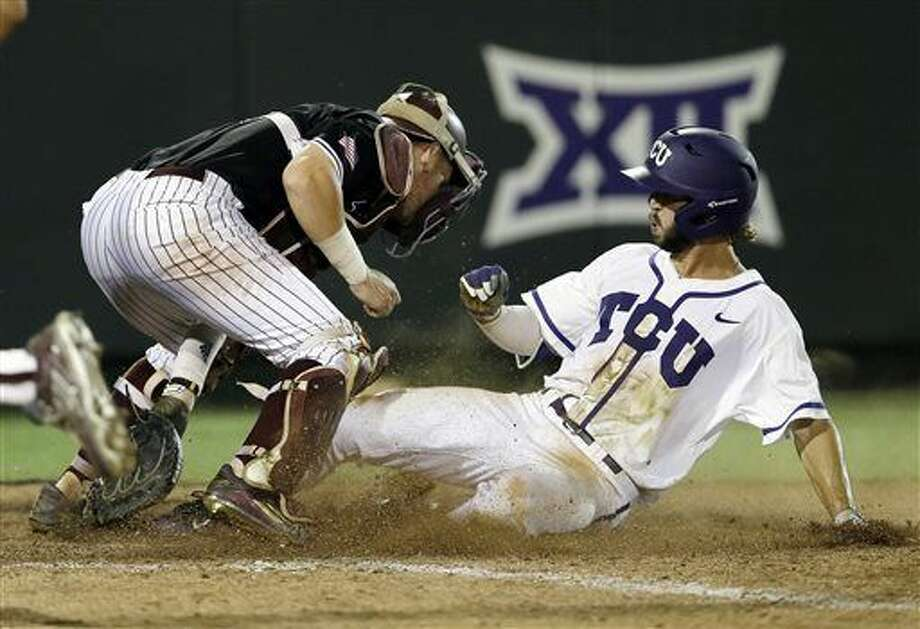 TCU's Garrett Crain, right, scores the winning run against Texas A&M catcher Michael Barash during the 16th inning of a super regional of the NCAA college baseball tournament in Fort Worth on Monday. TCU won 5-4. (AP Photo/Tim Sharp) Photo: Tim Sharp