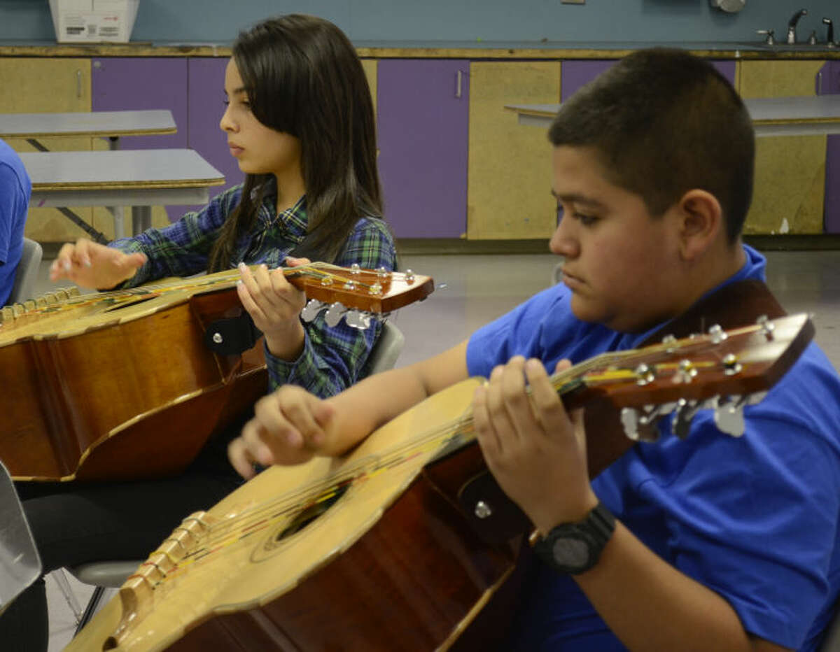 Leslie Perez and Adrian Marquez practice the guitarron during the Midland Hispanic Cultural Center's mariachi workshop on June 12, 2014.