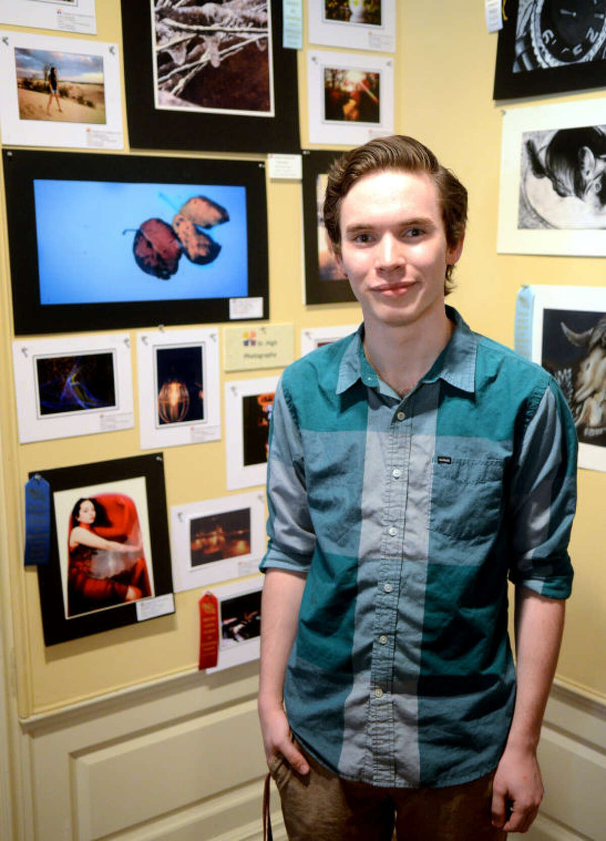 Kolton Cotton stands with photography work on display at the 2014 Student Art Exhibition in the Turner-Thomas Galleries and the Durham Children's Museum on April 3. His picture, bottom left of frame, won first place. James Durbin/Reporter-Telegram