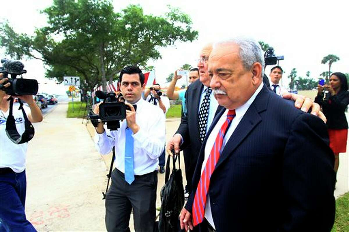 Former Hidalgo County Sheriff Lupe Trevino walks past members of the media with his attorney Robert Yzaguirre after leaving the McAllen Federal Court building, Monday, April 14, 2014, in McAllen, Texas. Trevino pleaded guilty Monday to money laundering and faces a 20-year sentence. He was released on a $30,000 unsecured bond Monday. (AP Photo/The Monitor, Gabe Hernandez)