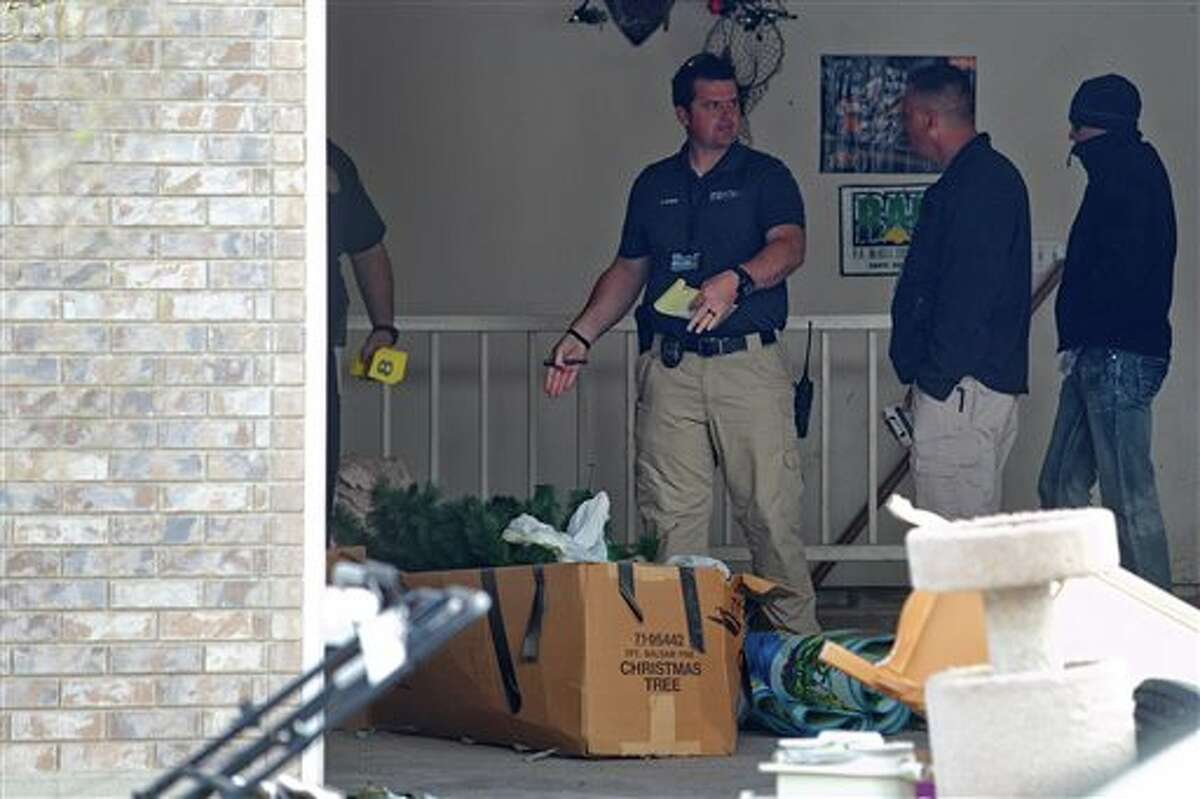 Authorities investigate a crime scene at a house in Pleasant Grove, Utah, Sunday, April 13, 2014. According to the Pleasant Grove Police Department, seven dead infants were found in the former home of Megan Huntsman, 39. Huntsman was booked into jail on six counts of murder. (AP Photo/Daily Herald, Mark Johnston)