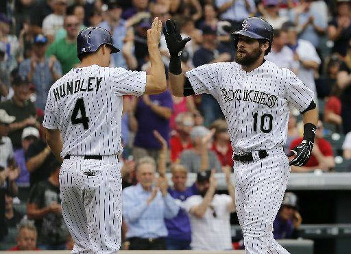 Colorado Rockies' Ben Paulsen (10) is congratulated by Nick Hundley (4) after hitting a two run-home run against the St. Louis Cardinals during the seventh inning of a baseball game Wednesday, June 10, 2015, in Denver. (AP Photo/Jack Dempsey)