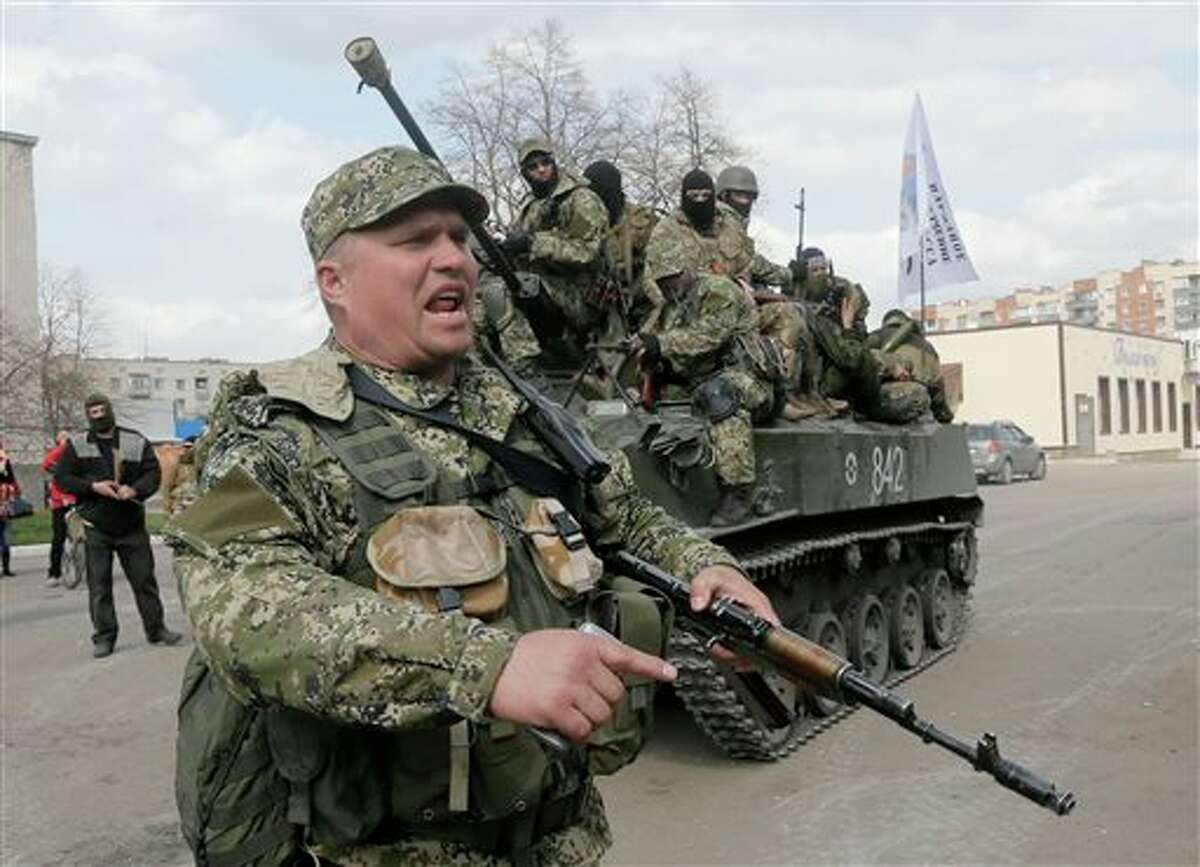 A pro-Russian gunman clears the way for a combat vehicle with gunmen on top in Slovyansk, Ukraine, Wednesday, April 16, 2014. The troops on those vehicles wore green camouflage uniforms, had automatic weapons and grenade launchers. At least one had the St. George ribbon attached to his uniform, which has become a symbol of the pro-Russian insurgency in eastern Ukraine. (AP Photo/Efrem Lukatsky)