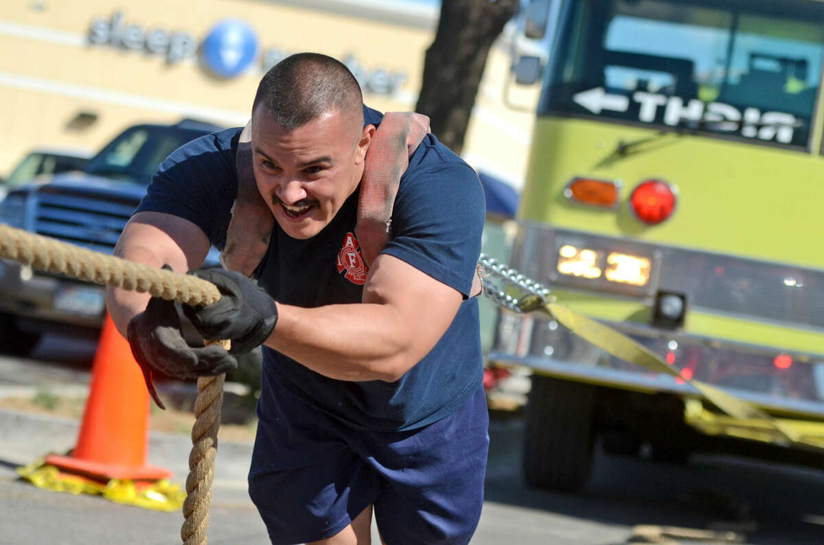Richard Mendoza, a fireman with Station 9, pulls a fire truck in the Heroes Fitness parking lot located near North Loop 250 on Saturday, May 2, 2015, during a demonstration put on by the Midland Fire Department in preparation for the upcoming Strong Man/Woman competition. James Durbin/Reporter-Telegram