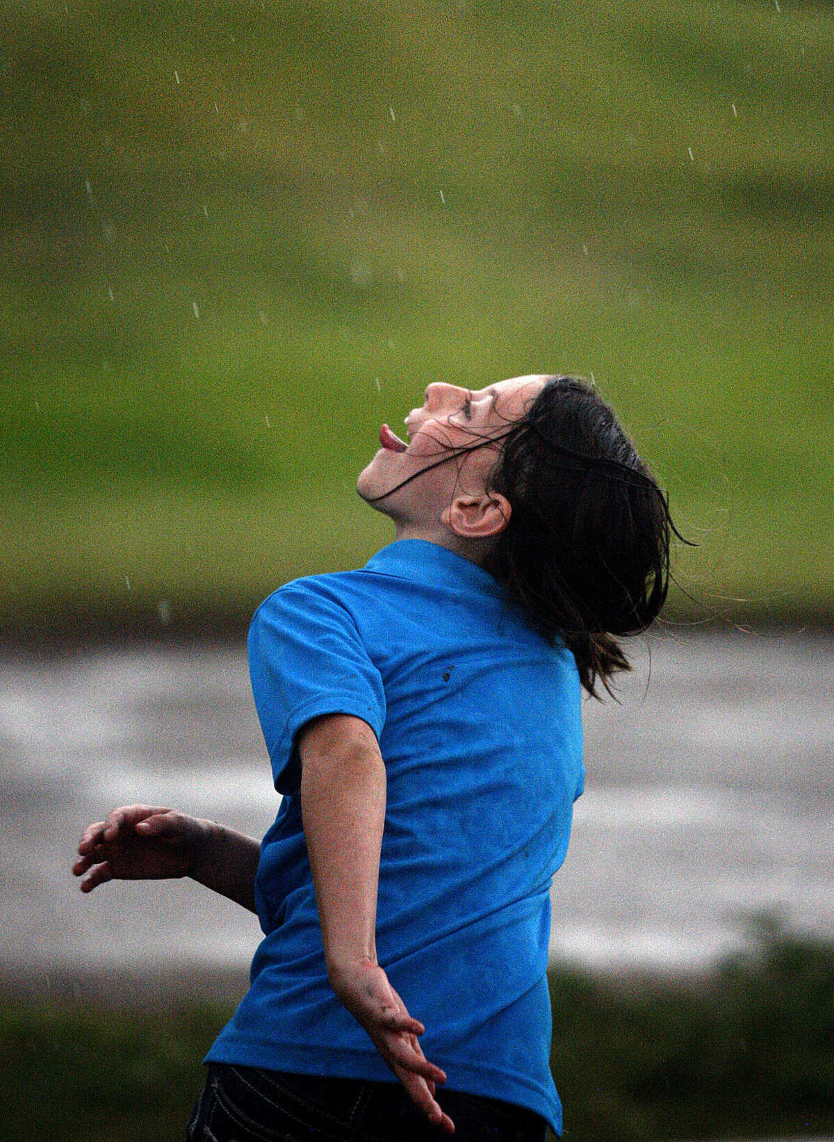Hope Gleghorn, age 8, catches rain drops at Hogan Park Golf Course as a thunderstorm rolls through the Permian Basin on Friday, June 12, 2015. James Durbin/Reporter-Telegram