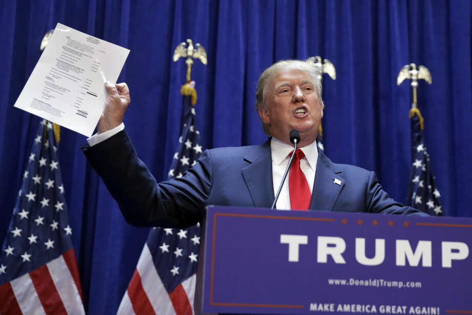 Developer Donald Trump displays a copy of his net worth during his announcement that he will seek the Republican nomination for president, Tuesday, June 16, 2015, in the lobby of Trump Tower in New York. (AP Photo/Richard Drew) Photo: Richard Drew