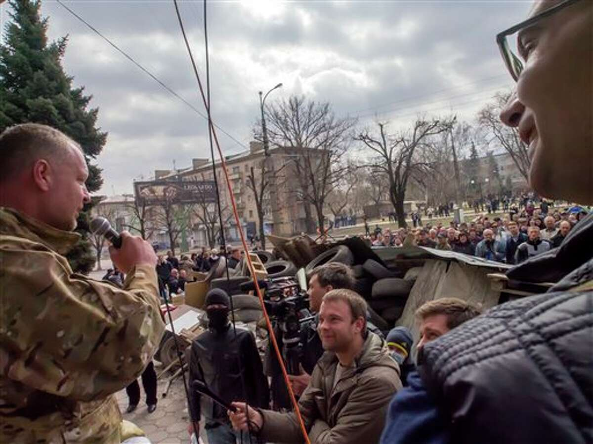 A pro-Russian activist, who said his name is Vasily, left, speaks to other protesters at barricades in front of an entrance of the Ukrainian regional office of the Security Service in Luhansk, 30 kilometers (20 miles) west of the Russian border, in Ukraine, Wednesday, April 9, 2014. Ukrainian Interior Minister Arsen Avakov said the standoff in Luhansk and the two neighboring Russian-leaning regions of Donetsk and Kharkiv must be resolved within the next two days either through negotiations or through the use of force, the Interfax news agency reported. (AP Photo/Igor Golovniov)