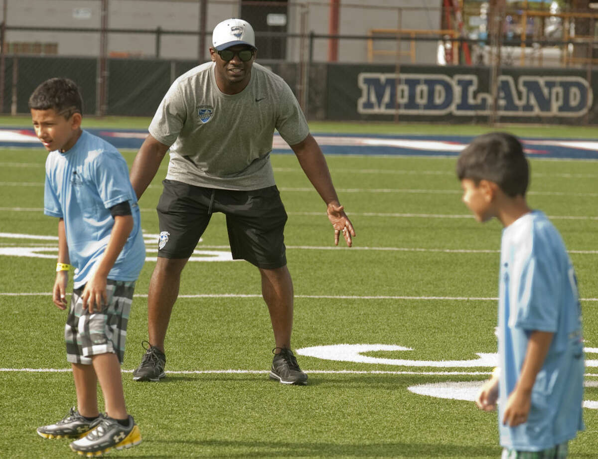 LaDainian Tomlinson works with students as they run football drills Wednesday, 6-17-15, during the LaDainian Tomlinson Preparatory Academy with the Midland Boys and Girls Club at Midland Christian's Mustang Field. Tim Fischer\Reporter-Telegram